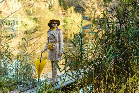 attractive elegant woman in sunglasses, trench coat and hat posing with yellow umbrella near pond in park