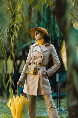 selective focus of woman in sunglasses, trench coat and hat posing with yellow umbrella outdoors