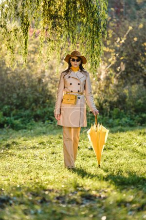 elegant young woman in sunglasses, trench coat and hat posing with yellow umbrella on meadow