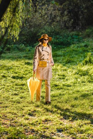 attractive stylish woman in sunglasses, trench coat and hat posing with yellow umbrella on meadow