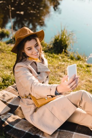 joyeuse belle femme élégante chapeau tenant selfie sur smartphone à l'extérieur