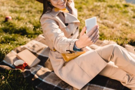 partial view of stylish woman in hat taking selfie on smartphone outdoors