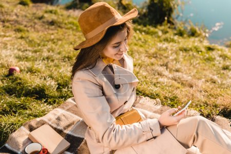 high angle view of smiling fashionable woman in hat using smartphone while sitting on blanket outdoors