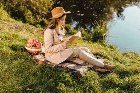 Photo for Side view of stylish beautiful woman in hat reading book on blanket near pond outdoors - Royalty Free Image