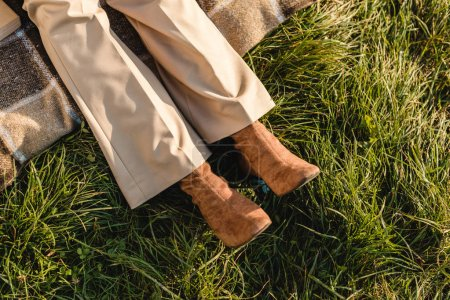 low section of female legs in suede brown shoes on grass outdoors
