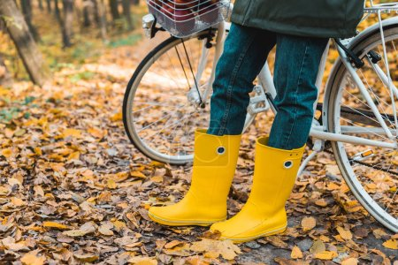 cropped image of woman in yellow rubber boots standing near bicycle in autumnal park