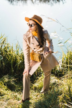 elegant stylish woman in trench coat, hat and sunglasses posing near pond outdoors