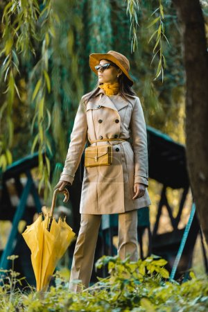 fashionable young woman in trench coat and hat posing with yellow umbrella outdoors