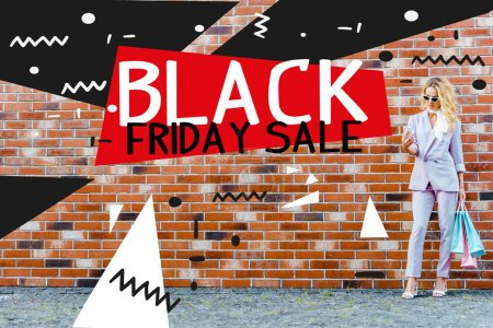 stylish young woman with shopping bags using smartphone while standing in front of brick wall, black friday sale banner