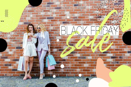 shocked young women with shopping bags taking selfie while standing in front of brick wall, black friday sale banner