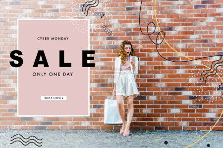 shocked young woman with shopping bags using smartphone in front of brick wall, cyber monday banner