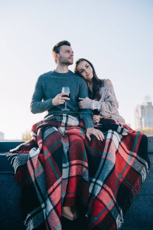 bottom view of beautiful young couple covering in plaid and drinking red wine on rooftop