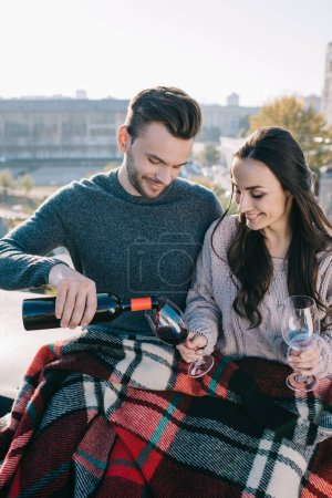happy young couple covering in plaid on rooftop and pouting red wine into glasses