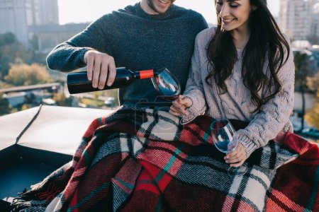 cropped shot of happy young couple covering in plaid on rooftop and pouting red wine into glasses