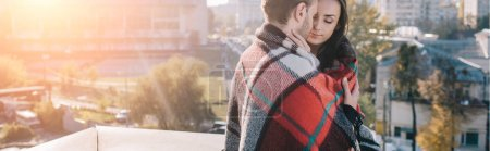 panoramic shot of beautiful young couple covering in plaid and cuddling on rooftop