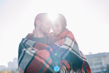 Photo pour Beau jeune couple couvrant en plaid et câlins avec soleil brillant derrière - image libre de droit