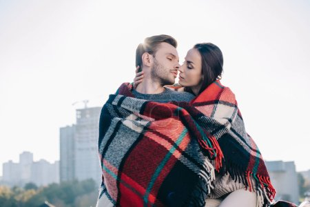 beautiful young couple covering in plaid and kissing with sun shining behind
