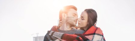 Photo for Panoramic shot of beautiful young couple covering in plaid and kissing with sun shining behind - Royalty Free Image