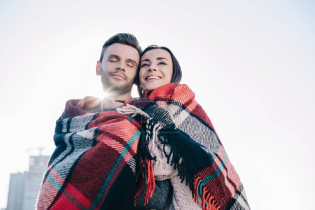 bottom view of beautiful young couple covering in plaid and embracing with sun shining behind