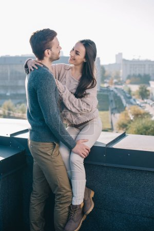 smiling young couple embracing and looking at each other on rooftop