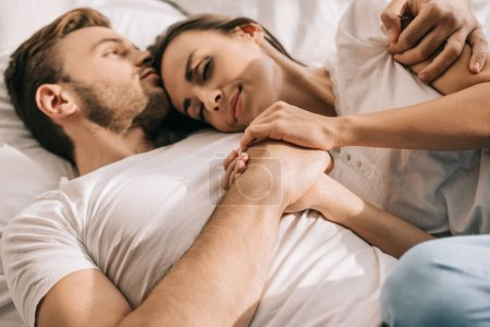 Photo for Beautiful young couple in pajamas holding hands in bed in morning - Royalty Free Image