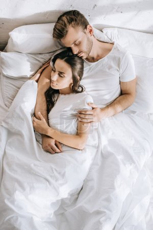 top view of beautiful young couple sleeping in bed in morning