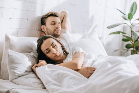 attractive young couple sleeping in bed in morning