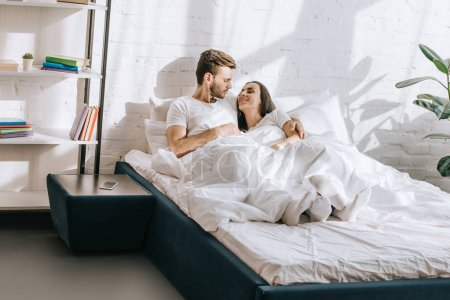beautiful young couple relaxing and chatting in bed in morning