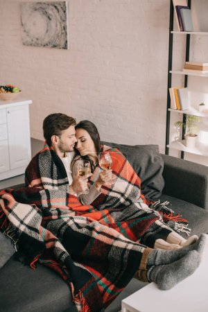 high angle view of beautiful young couple with glasses of white wine relaxing on couch under plaid