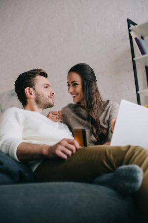 bottom view of happy young couple making e-shopping with laptop on couch at home
