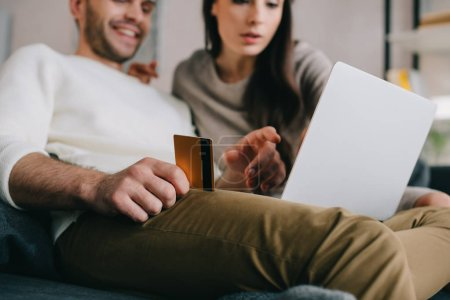 beautiful young couple making e-shopping with golden credit card and laptop on couch at home