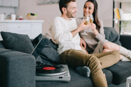 Photo for Happy young couple listening music with vinyl record player and drinking wine at home - Royalty Free Image