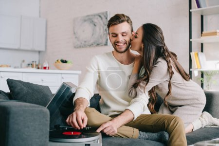 Photo for Happy young couple listening music with vinyl record player and cuddling at home - Royalty Free Image