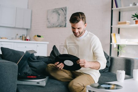 Photo for Handsome young man holding disc for vinyl record player while sitting on couch - Royalty Free Image