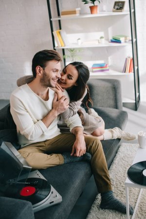 Photo for Beautiful young couple listening music with vinyl record player and cuddling at home - Royalty Free Image