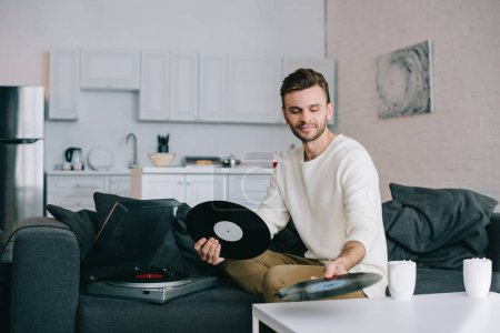 attractive young man holding discs for vinyl record player while sitting on couch