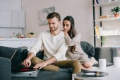 beautiful young couple listening music with vinyl record player at home