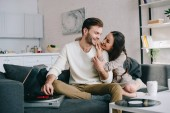 beautiful young couple listening music with vinyl phonograph and cuddling on couch