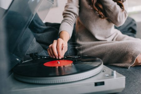 cropped shot of woman listening music with vinyl record player on couch at home