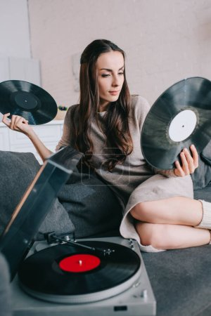 beautiful young woman holding discs for vinyl record player on couch at home