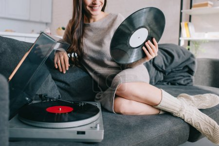 Photo for Cropped shot of young woman listening music with vinyl record player on couch at home - Royalty Free Image