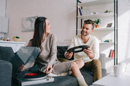 Photo for Happy young couple listening music with vinyl phonograph at home - Royalty Free Image