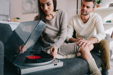 beautiful young couple listening music with vinyl phonograph at home