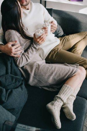 Foto de Toma recortada de pareja con tazas de cacao en caliente lana calcetines relax en el sofá en casa - Imagen libre de derechos