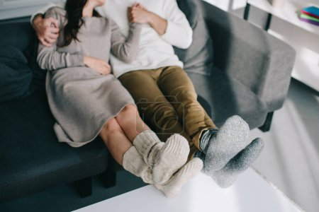 cropped shot of couple in warm woolen socks relaxing on couch at home