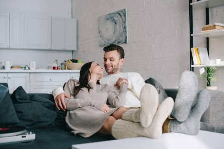 Photo for Happy couple in woolen socks relaxing on couch at home - Royalty Free Image