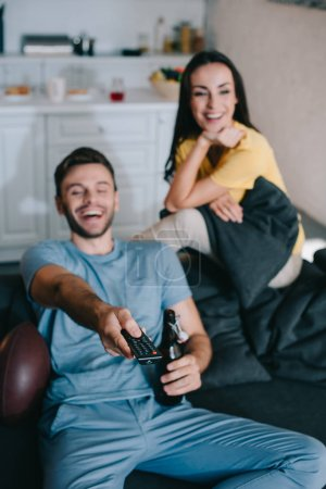 Photo for Happy young couple watching american football game at home - Royalty Free Image