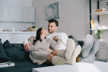 romantyczna para młodych w wełniane skarpety, relaksując się na kanapie w domu