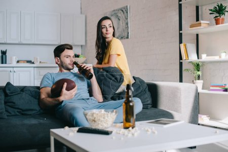Photo for Smiling young couple watching american football game at home - Royalty Free Image