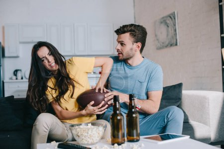 angry young woman fighting for american football ball with husband during match on tv at home